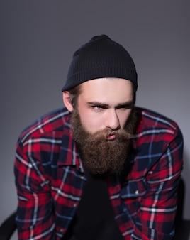 Hipster barbudo em camisa xadrez, olhando para longe. foto com espaço de cópia