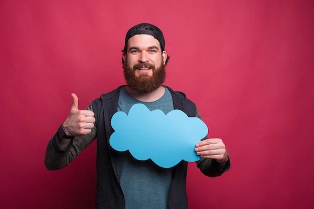 Hipster barbudo está segurando uma nuvem azul e mostrando o polegar para cima gesto