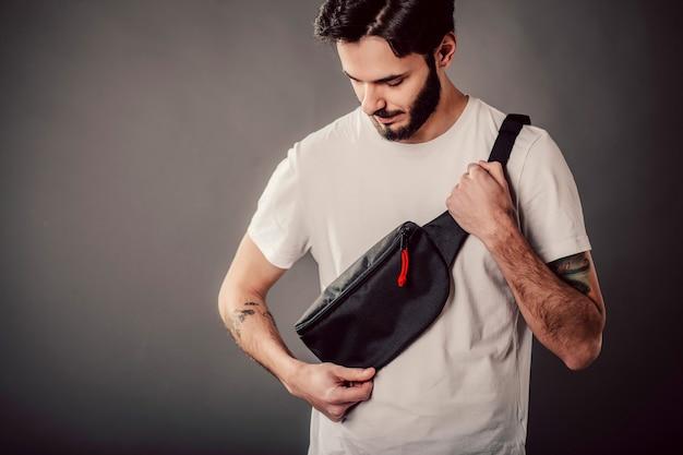 Hipster barbudo estiloso no estúdio em uma camiseta branca com bolsa na cintura