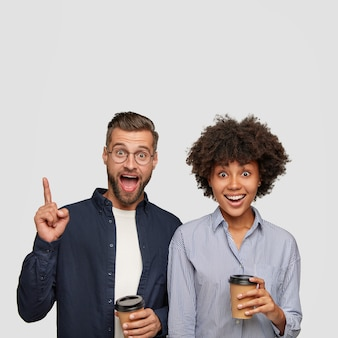 Hipster barbudo feliz apontando com o dedo indicador para cima, perto de sua namorada morena