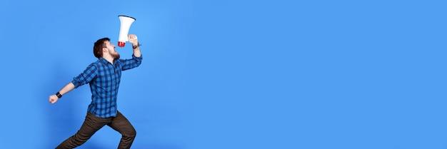 Hipster barbudo gritando em um megafone em uma parede azul, imagem panorâmica com lugar para texto