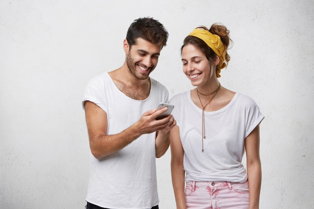 Hipster barbudo jovem feliz segurando o telefone inteligente, mostrando fotos ou vídeos engraçados da namorada. casal europeu despreocupado e despreocupado usando conexão de alta velocidade à internet em dispositivo eletrônico