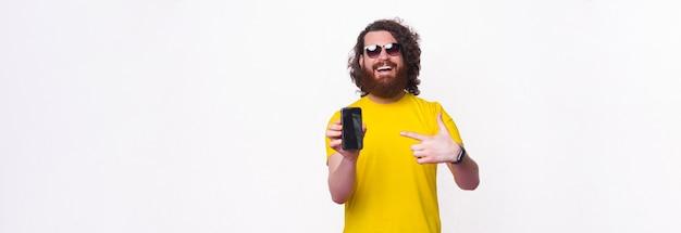 Hipster barbudo legal está apresentando a oferta na tela do telefone.