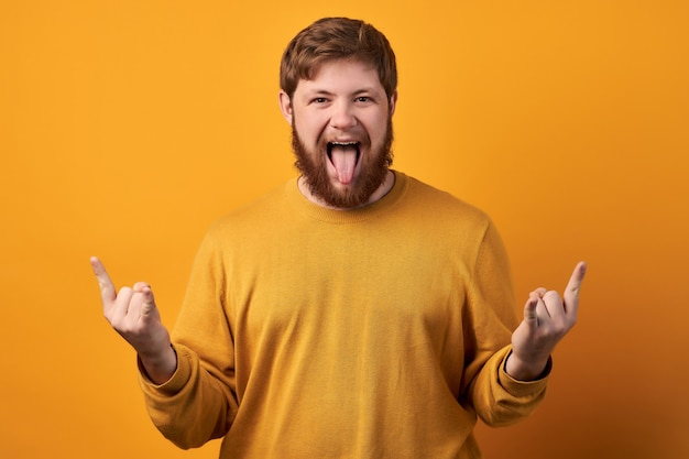 Hipster barbudo louco gosta de festa de rock, faz sinal de heavy metal e gosta de música legal