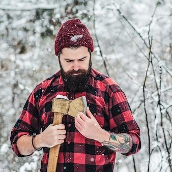 Hipster barbudo verifica lâmina de machado na floresta de inverno