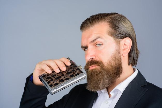 Hipster barbudo veste um terno elegante segurando um frasco de metal para o homem do álcool com seu frasco de bebida cavalheiro em