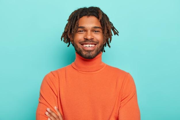 Hipster bonito com dreads tem sorriso agradável, dentes brancos, fica feliz em ouvir boas notícias, usa roupas brilhantes