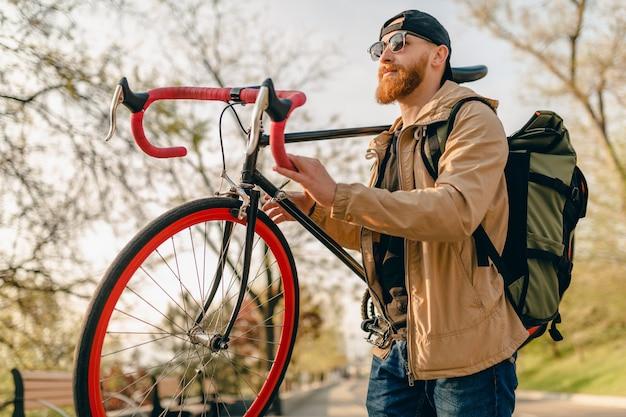 Hipster bonito elegante barbudo homem com jaqueta e óculos de sol andando sozinho na rua com mochila em bicicleta mochileiro viajante estilo de vida ativo saudável
