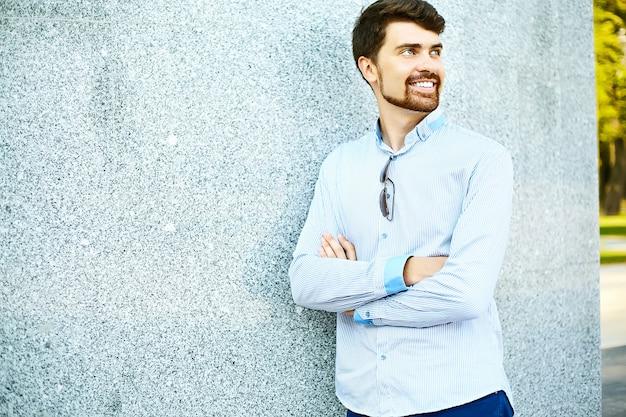 Hipster bonito jovem estudante do sexo masculino em pé perto da parede