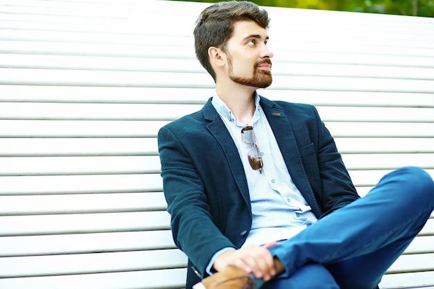 Hipster bonito jovem estudante do sexo masculino sentado no banco de um parque em terno