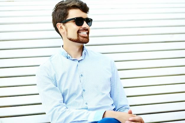 Hipster bonito jovem estudante do sexo masculino sentado no banco de um parque