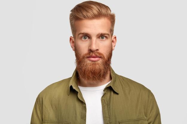 Hipster bonito tem barba ruiva, penteado moderno, olha sério diretamente para a câmera, contempla sobre um futuro emprego