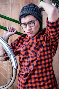Hipster carregando uma bicicleta nos ombros