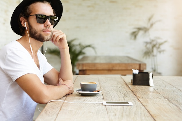 Hipster caucasiano bonito com chapéu da moda e óculos escuros, desfrutando de wi-fi grátis em uma cafeteria