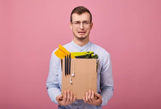 Hipster chateado legal em uma camisa azul céu e óculos de computador fica com uma caixa de papelão com coisas diferentes