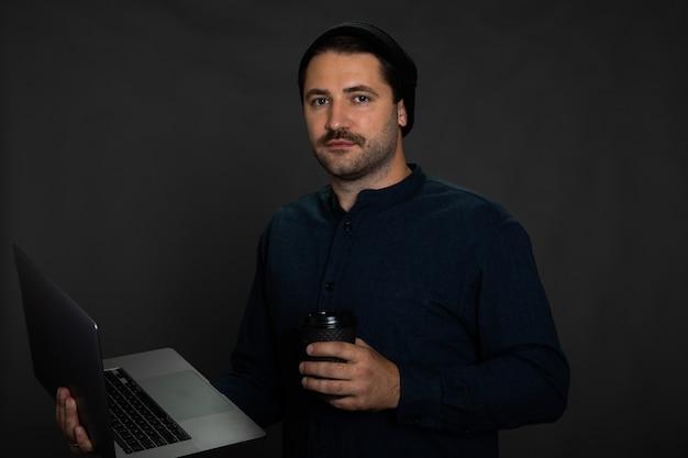 Hipster com barba por fazer posando em um estúdio cinza com laptop e xícara de café descartável