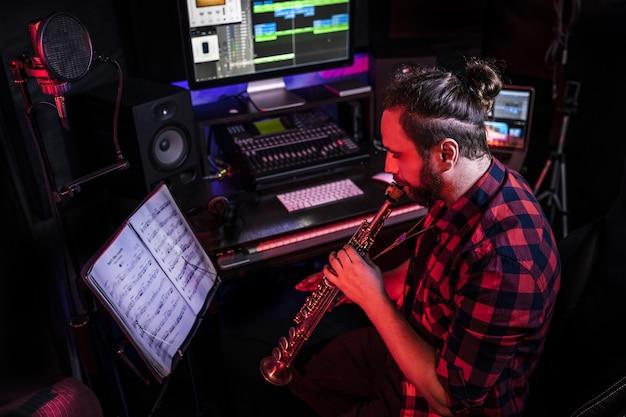 Hipster com o jovem está tocando um instrumento musical com composição no estúdio para gravar sua nova música.