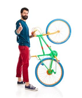 Hipster com o polegar para cima segurando uma bicicleta