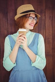 Hipster de cabelo vermelho bonito com óculos segurando copo descartável