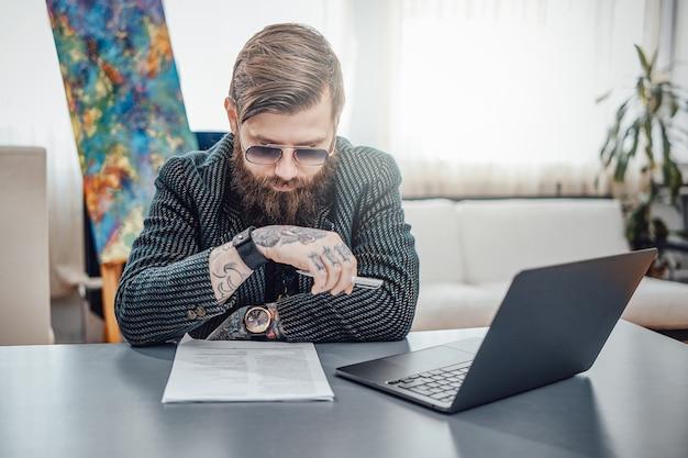 Hipster de elegância com um penteado elegante se senta à mesa com o laptop, olhando para seu braço tatuado em um apartamento moderno.