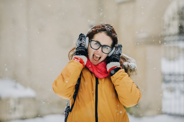 Hipster de garota muito atraente no inverno. ela está ouvindo música em fones de ouvido. moda de rua da juventude. diversão de inverno. passeios ao ar livre