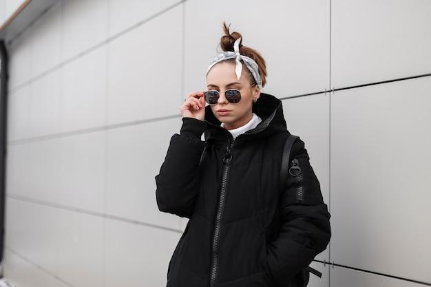 Hipster de mulher jovem na moda moderna com penteado elegante em óculos escuros em um casaco preto longo elegante com uma bandana com uma mochila de couro nos ombros se passando perto da parede. garota americana.