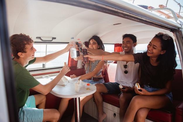 Hipster despreocupado se divertindo com um brinde de bebida dentro da van retrô