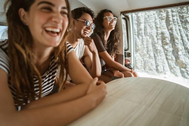 Hipster despreocupado se divertindo dentro de van retrô em viagem