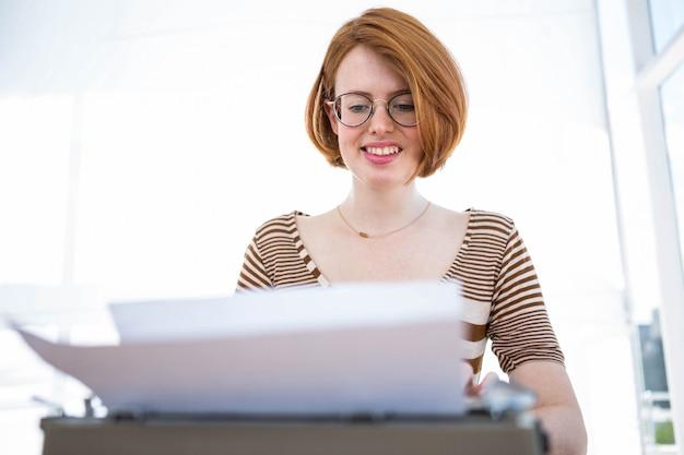 Hipster digitando em uma máquina de escrever que está em uma mesa de madeira