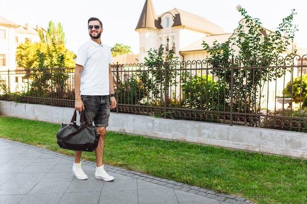 Hipster elegante com barba em uma camiseta branca, com uma mala de viagem nas mãos andando pela cidade