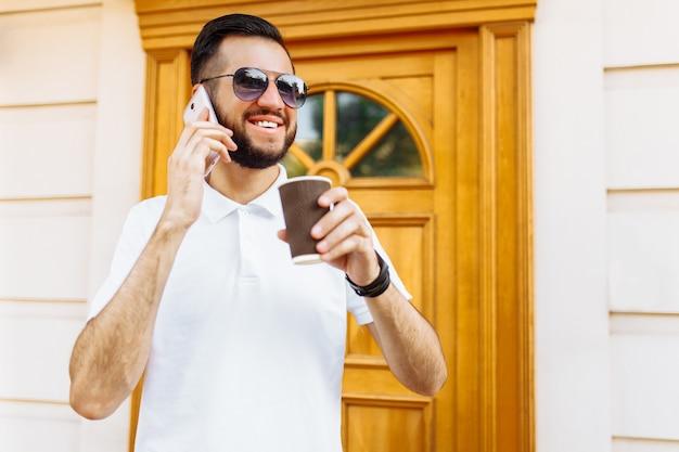 Hipster elegante em uma camisa branca e óculos de sol, na parede de um edifício branco falando ao telefone e tomando café