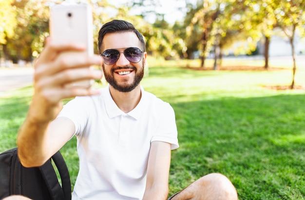 Hipster elegante em uma camisa branca senta-se no gramado do parque e tira uma selfie em seu smartphone