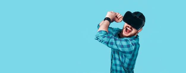 Hipster em óculos de realidade virtual emocionalmente joga o jogo, concebe novas tecnologias na vida moderna