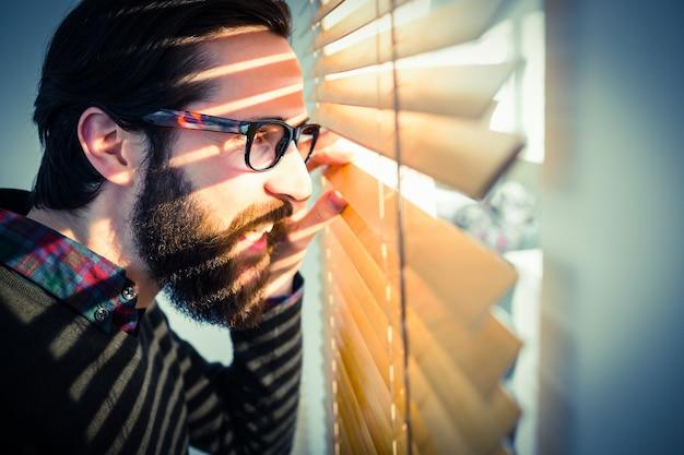 Hipster empresário espreitando através de persianas