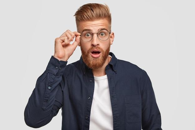 Hipster estupefato com expressão chocada, ouve algo inacreditável, mantém a mão na borda dos óculos redondos, abre a boca de surpresa, vestido com uma camisa estilosa, isolado na parede branca