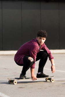 Hipster étnico na camisa quadriculada equitação skate cócoras