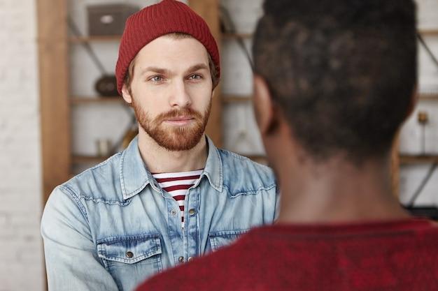 Hipster europeu barbudo bonito usando chapéu e jaqueta jeans, tendo uma conversa séria