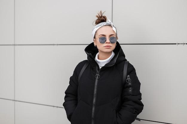 Hipster europeu elegante jovem no elegante casaco preto com um penteado moderno com uma elegante bandana posando na cidade perto de uma parede branca. roupas femininas no estilo americano.