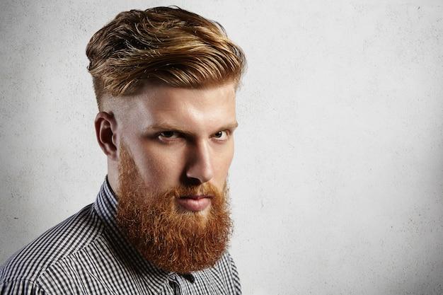 Hipster europeu viril na camisa olhando a sério. seu corte de cabelo estiloso e sua barba loira bem aparada dizem que ele é cliente fiel da barbearia e cuida de sua aparência.