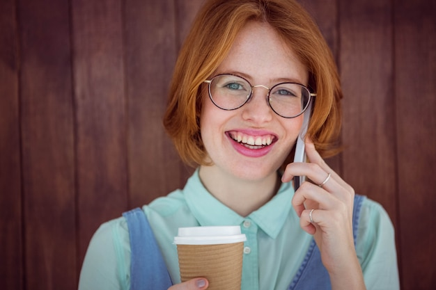 Hipster falando no telefone tomando café