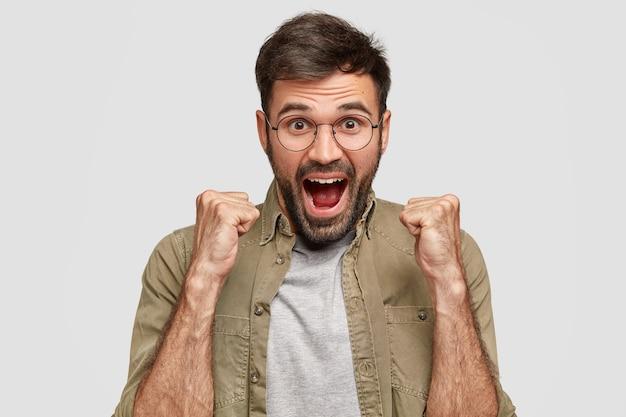 Hipster feliz com punhos cerrados e boca aberta parece alegre, comemora a vitória, usa óculos redondos e camisa da moda