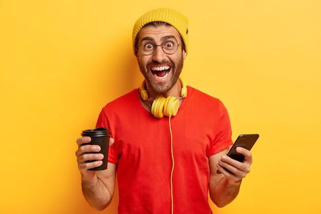 Hipster feliz cria novo perfil nas redes sociais, ri de felicidade, segura aparelho eletrônico moderno, bebe café