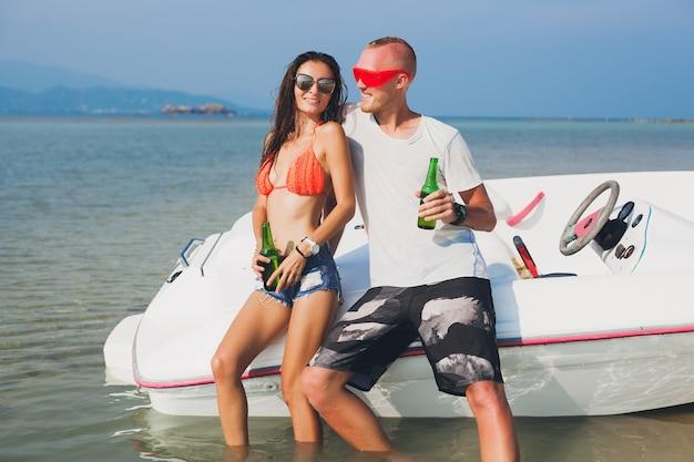 Hipster feliz mulher e homem bebendo cerveja nas férias tropicais de verão na tailândia, viajando em um barco no mar, festa na praia, pessoas se divertindo juntos, emoções positivas