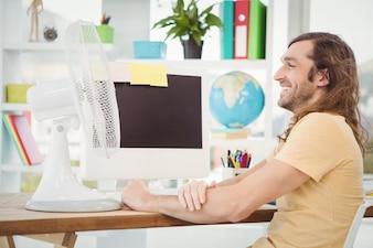 Hipster feliz sentado por ventilador elétrico na mesa do computador