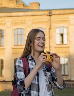 Hipster feliz viajante tirando foto, andando na rua, rindo. retrato do jovem fotógrafo segurando a câmera amarela