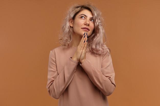 Hipster feminino atraente apertando as mãos e olhando para cima com um sorriso esperançoso, rezando
