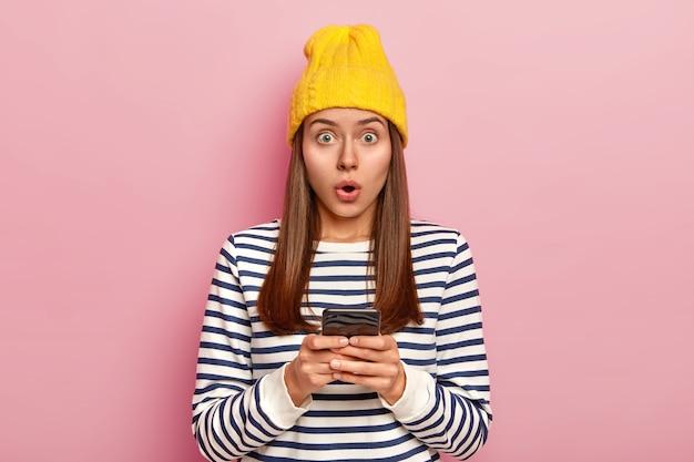 Hipster feminino europeu fascinado segurando um celular moderno, boquiaberto e engasgado de espanto, usa um chapéu amarelo e um macacão listrado, isolado sobre a parede rosa do estúdio