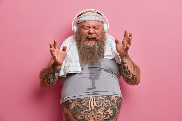 Hipster gordinho emotivo ouve música em fones de ouvido, canta música alto, vestido com roupas esportivas, tem treinamento físico para perder peso, posa contra uma parede rosada. atleta homem barbudo dentro de casa
