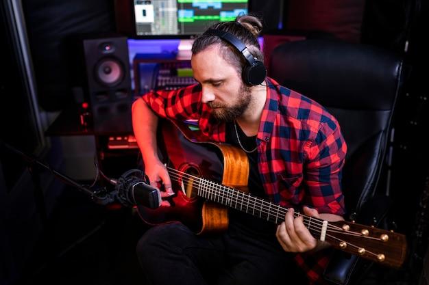 Hipster homem com barba no fone de ouvido está tocando guitarra e cantando sua nova música em estúdio estéreo para gravar uma nova faixa.