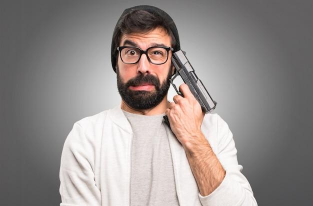 Hipster homem cometer suicídio em fundo cinza